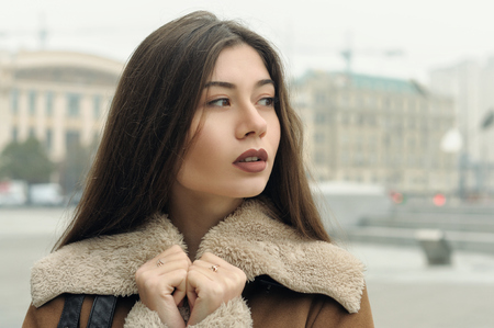 Close-up portrait of a girl who is walking around the city. The weather is cold and she is wearing a warm fur coat. Stock Photo