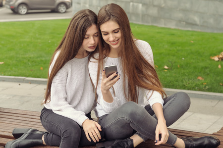 Two girlfriends are sitting on the bench and watching pictures in the smartphone. They both have long brown hair that is long to the waist and they are dressed in identical white sweaters.