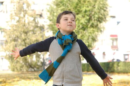 Boy running across the yard from the joyful feeling of freedom. A long scarf is tied around the boy's neck