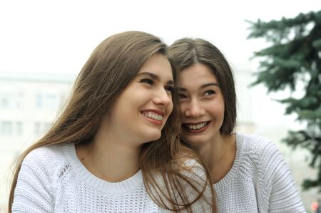 Two girlfriends are laughing fun. They both have long brown hair that is long to the waist and they are dressed in identical white sweaters.