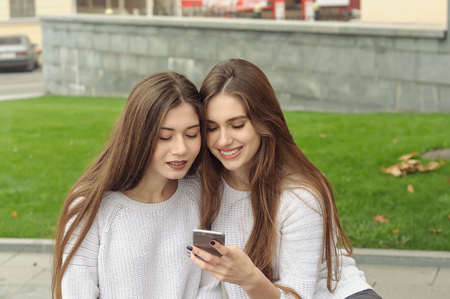 Two brunettes look at photos on their smartphone and laugh. They both have long brown hair that is long to the waist and they are dressed in identical white sweaters. Stock Photo - 91494871