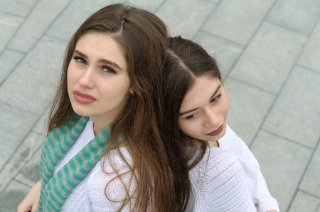 Two girlfriends make a selfie photo, standing with their backs to each other. They both have long brown hair that is long to the waist and they are dressed in identical white sweaters. Stock Photo