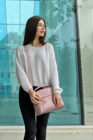 Beautiful brunette with long hair standing with a pink handbag near a glass case. She is dressed in black jeans and a white sweater.