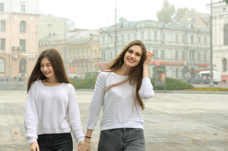Two girlfriends are walking around the square holding hands and laughing. They both have long brown hair and they are dressed in identical white sweaters against the background of buildings in the fog.