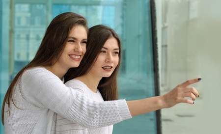 Girl shows her friend a finger at something interesting and smiles. They both have long brown hair that is long to the waist and they are dressed in identical white sweaters.