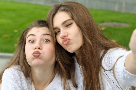 Two friends inflated cheeks while doing selfie photo. They both have long brown hair that is long to the waist and they are dressed in identical white sweaters.