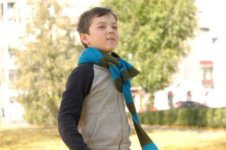 Boy walking in the park on a joyful sense of freedom. A long scarf is tied around the boy's neck Stock Photo