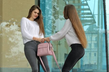 Two friends pull each other's favorite handbag. They both have long brown hair that is long to the waist and they are dressed in identical white sweaters.
