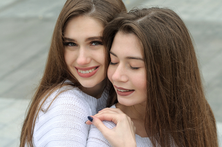 Close-up portrait of two brunettes. They both have long brown hair that is long to the waist and they are dressed in identical white sweaters. Stock Photo - 91494874