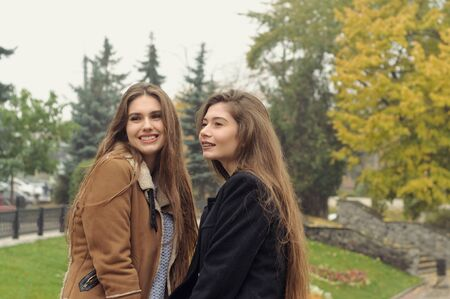 Two students walk in the autumn park and have fun. They have long brown hair and look fashionable and modern