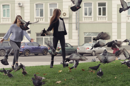 Two girlfriends chase pigeons in the park. They fool around and have fun, because they have a good mood