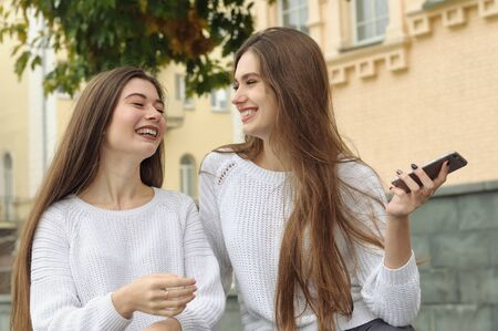 Two brunettes laugh happily during a conversation, waving a smartphone. They both have long brown hair that is long to the waist and they are dressed in identical white sweaters. Stock Photo - 91283192