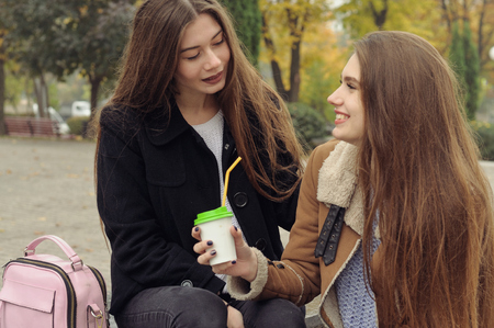 Two girlfriends try to warm up with a hot drink in the outdoors. They are having fun and fooling around, talking on the smartphone and sharing events with each other Stock Photo - 91494876