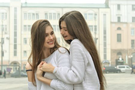 Two girlfriends are holding hands and fooling around in the city center. They both have long brown hair that is long to the waist and they are dressed in identical white sweaters.