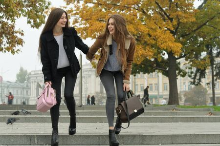 Girlfriends have fun and run down the steps of the sidewalk as they walk down the street. They are fashionable, modern and fun student Stock Photo