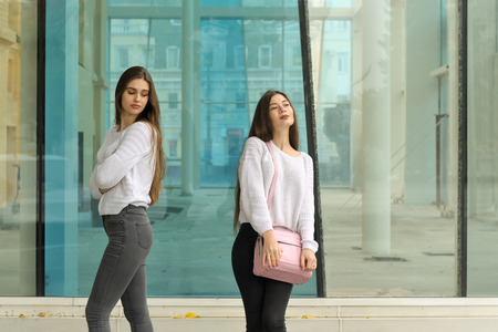 Girl with envy looks at her friend's handbag. They both have long brown hair that is long to the waist and they are dressed in identical white sweaters. Stock Photo