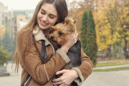 Girl holds a small dog in her arms, hugs and kisses her, warming her from the autumn cold.