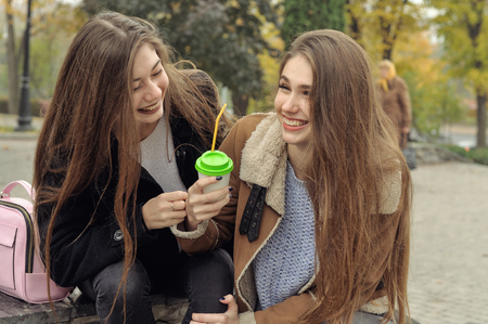 Two girlfriends try to warm up with a hot drink in the outdoors. They are having fun and fooling around, talking on the smartphone and sharing events with each other Stock Photo - 91283195