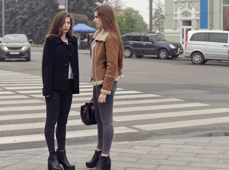 Two girls trying to cross the road at a pedestrian crossing. They have long brown hair and slender figures. Stock Photo