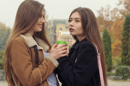 Two girlfriends try to warm up with a hot drink in the outdoors. They are having fun and fooling around, talking on the smartphone and sharing events with each other Stock Photo