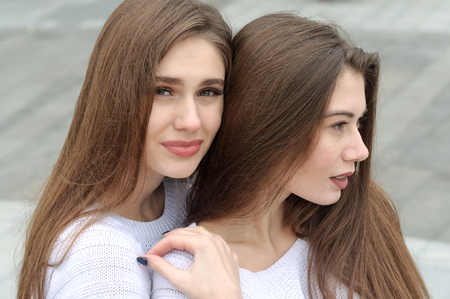 Close-up portrait of two close friends. They both have long brown hair that is long to the waist and they are dressed in identical white sweaters. Stock Photo