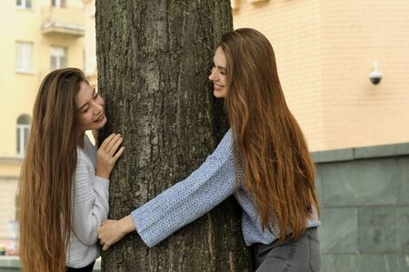 Two friends are fooling around, looking out from behind a tree. They have long brown hair, they are having fun and laughing