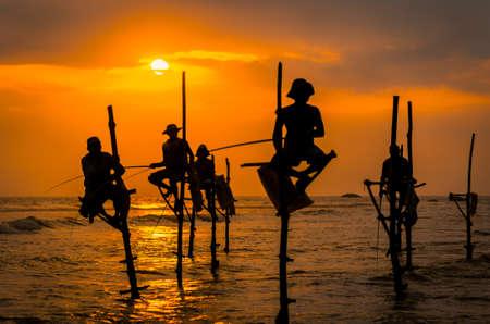 Silhouetten van de traditionele vissers bij de zonsondergang in Sri Lanka