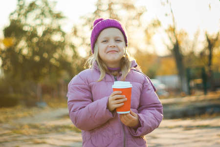 Cute little girl drinks hot chocolate in autumn park in surround of yellow