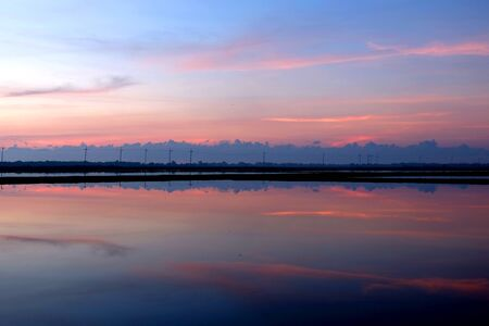 evaporation: The salt pans or salt evaporation pond reflected the blue sky and the electric pole line in blue and pink color in the early morning.