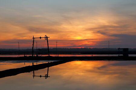 evaporacion: El estanque salinas o evaporación de sal refleja el molino de viento en el fondo de color ámbar debido a la subida del sol por la mañana temprano.