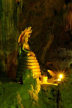 dark cave: Golden Buddha image is placed peacefully in a dark cave with the candle light. Stock Photo