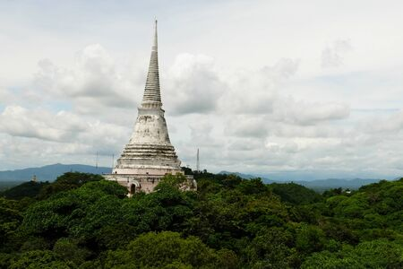 White Pagoda is allocated on the hill that cover with big green tree. The white cloud cover the blue sky sets as background of the Pagoda. Stock Photo