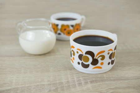 Two small retro coffee cups filled with black coffee, milk jar on a wood table.