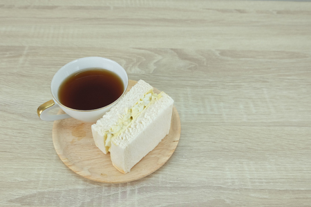 White tea cup with sandwich on wood tray are placed at the corner of a wood table. Archivio Fotografico