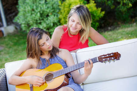 beautiful girl playing guitar in a garden with her mom