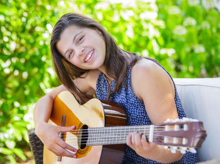Portrait of very handsome teenager playing guitar in her garden