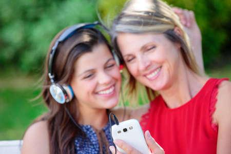personas escuchando: ni�a preciosa con su madre escuchando m�sica juntos con la complicidad