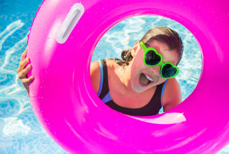 happy teenager playing on a buoy in a pool with sunglasses Archivio Fotografico