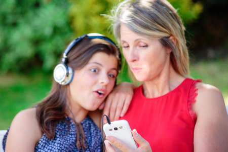 complicity: beautful young girl with her mother listening music together with complicity