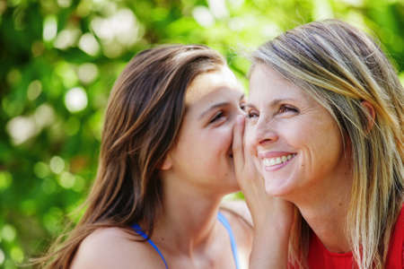 Pretty young brunette whispering in the ear of her mother