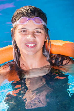 exercice: pretty young girl smiling in a swimming pool with pink swimming goggles on the head