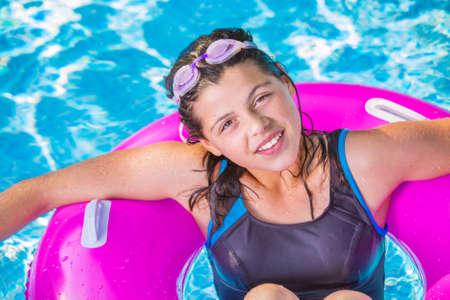 bathe mug: pretty girl smiling on a pink buoy in a swimming pool