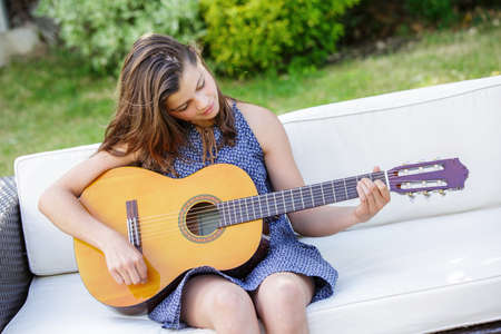 Portrait of very handsome teenager playing guitar in her garden Zdjęcie Seryjne - 42063411