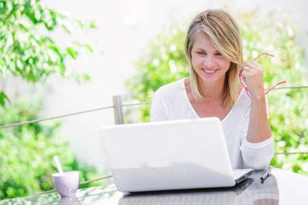 mujer trabajadora: hermosa mujer que trabaja en un ordenador en casa con jard�n verde en su fondo Foto de archivo