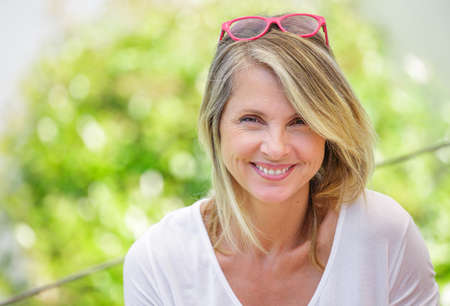 Portret van mooie blonde vrouw van middelbare leeftijd glimlachend in glazen