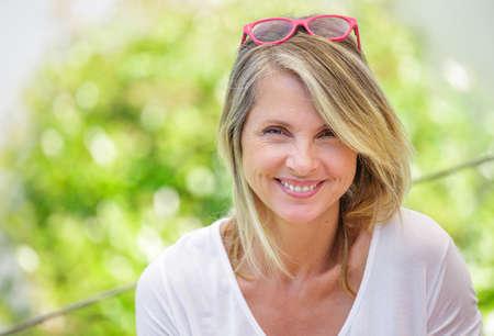 single woman: Retrato de mujer encantadora rubia de mediana edad sonriendo en gafas