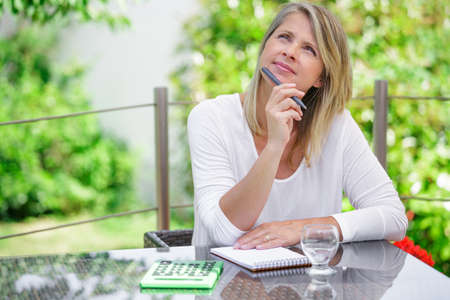 mujer reflexionando: mujer rubia de mediana edad que trabajan en casa sin estrés Foto de archivo
