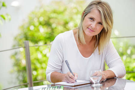 contemplating: middle aged blond woman working at home without stress Stock Photo