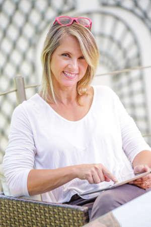 pretty blond woman looking at a digital tablet Standard-Bild