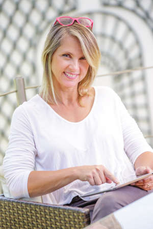 pretty blond woman looking at a digital tablet Banque d'images